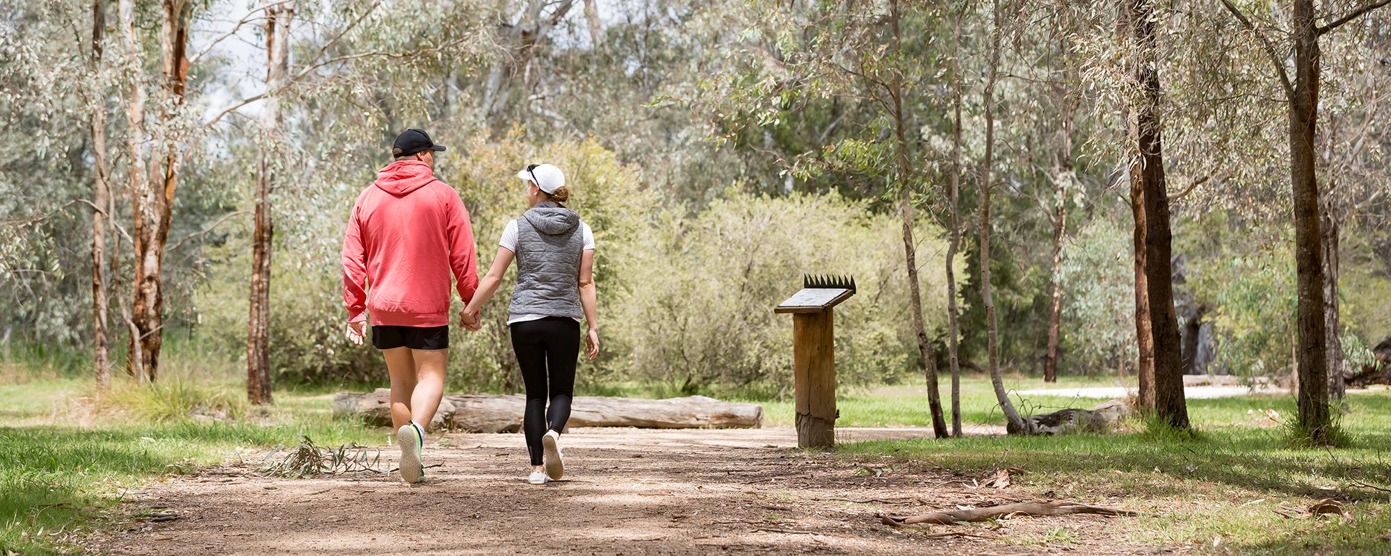 A couple walking along a Wonda Wetlands trail.